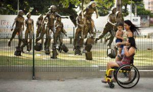 As sobreviventes Thayane Tavares e Brenda Rocha, com seu filho Nathan, passam na frente das esculturas que homenageiam os alunos que morreram no massacre Foto: Mônica Imbuzeiro / Agência O Globo